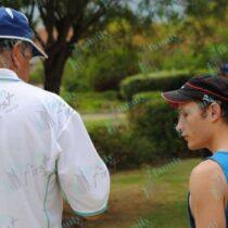 Man teaching young man to play jukskei