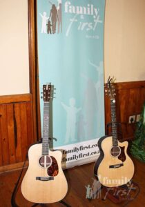 Two acoustic guitars before Family First banner